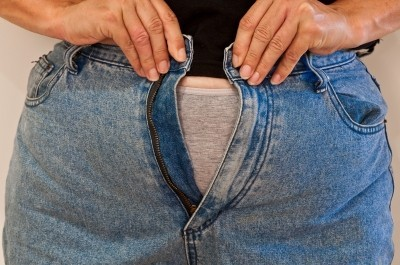 Woman trying to button jeans