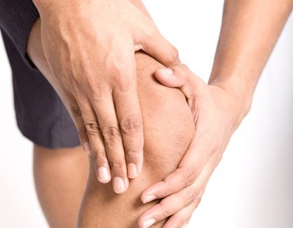 Close up of a man's hands holding his injured knee