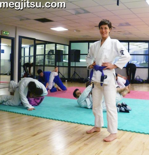 Meg poses in Fenom Lotus ripstop pants in front of pairs of sparring BJJers